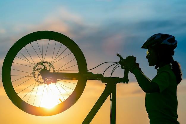 夕焼け空を背景に自転車と女性サイクリストのシルエット。健康的なライフスタイルとスポーツ。レジャーと趣味