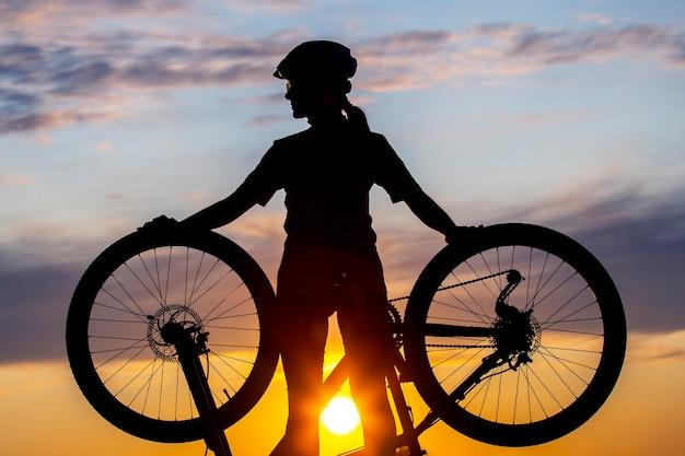 일몰 하늘 배경에 자전거와 여자 사이클의 실루엣