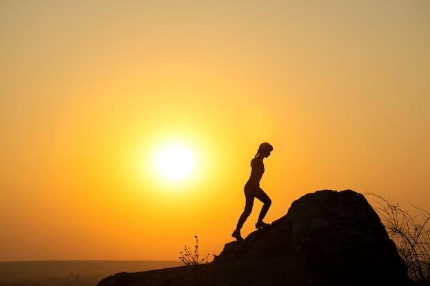 산에서 일몰에 큰 돌을 등반 여자 등산객의 실루엣. 저녁 자연에서 높은 바위에 여성 관광. 관광, 여행 및 건강한 라이프 스타일 개념.
