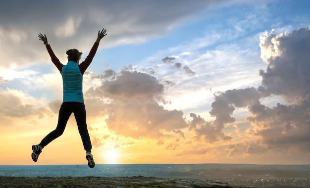 Силуэт туриста женщины прыгает в одиночку на пустом поле на закате в горах.
