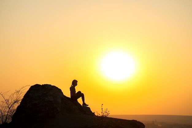 산에서 석양 큰 돌에 혼자 앉아 여자 등산객의 실루엣. 저녁 자연에서 높은 바위에 여성 관광.