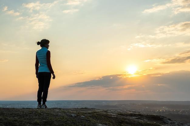 야외에서 일몰을 즐기는 혼자 서 있는 여성 등산객의 실루엣. 저녁 자연에서 농촌 필드에 여성 관광입니다. 관광, 여행 및 건강한 라이프 스타일 개념.
