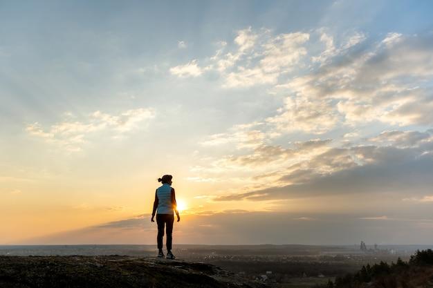 屋外で夕日を楽しんで一人で立っている女性ハイカーのシルエット。夜の自然の田園地帯の女性観光客。観光、旅行、健康的なライフスタイルのコンセプト。