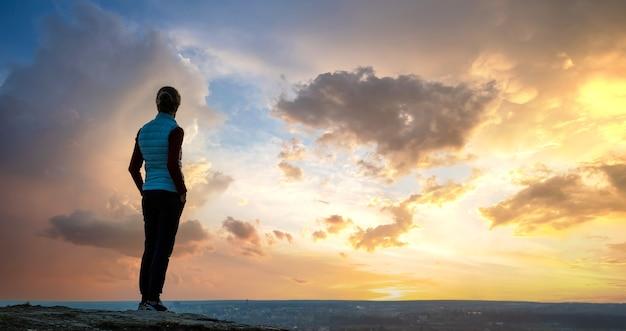 야외에서 일몰을 즐기는 혼자 서 있는 여성 등산객의 실루엣.