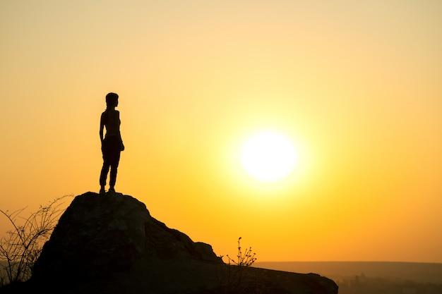 산에서 석양 큰 돌에 혼자 서있는 여자 등산객의 실루엣. 저녁 자연에서 높은 바위에 여성 관광.
