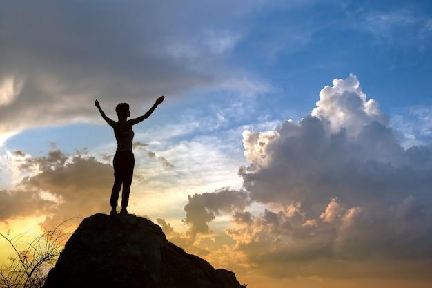 산에서 일몰에 큰 돌에 혼자 서있는 여자 등산객의 실루엣. 저녁 자연에 높은 바위에 그녀의 손을 키우는 여성 관광. 관광, 여행 및 건강한 라이프 스타일 개념.