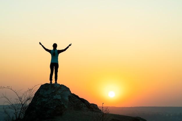 山の日没時に大きな石の上に一人で立っている女性ハイカーのシルエット。夕方の自然の中で高い岩の上に手を上げる女性観光客。観光、旅行、健康的なライフスタイルのコンセプト。