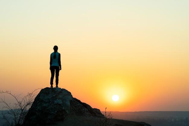 산에서 일몰에 큰 돌에 혼자 서있는 여자 등산객의 실루엣.
