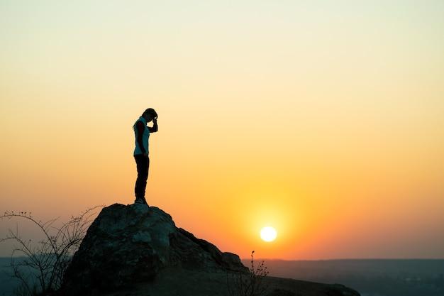 산에서 석양 큰 돌에 혼자 서있는 여자 등산객의 실루엣