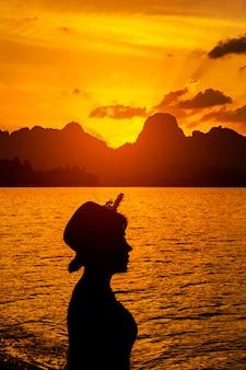 山に沈む夕日に対して立っている女性のプロファイルのシルエット