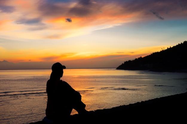해변에 앉아있는 여자의 실루엣
