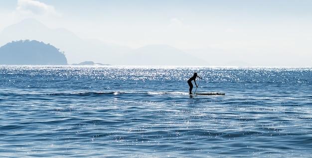 ブラジルの海でサーフィンをしている女性のスタンドアップパドルボードのシルエット