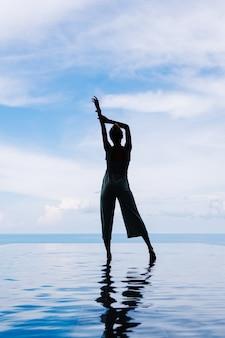 海の見える山にある高価で豪華な別荘のインフィニティプールの水面を歩く女性のシルエット