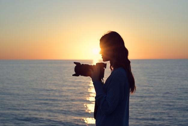 Силуэт женщины с фотоаппаратом на закате у моря сбоку. фото высокого качества