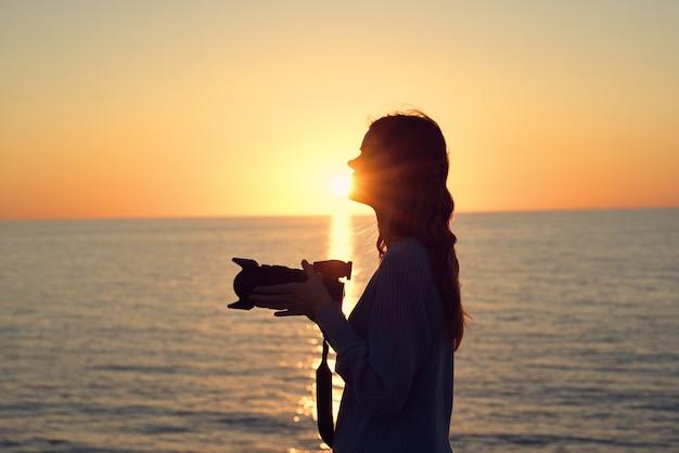 海の側面図の近くの日没時のカメラを持つ女性のシルエット。高品質の写真