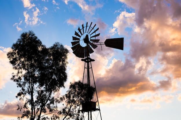 日没の光や夕暮れの中で働くヴィンテージの国の風車のシルエット。