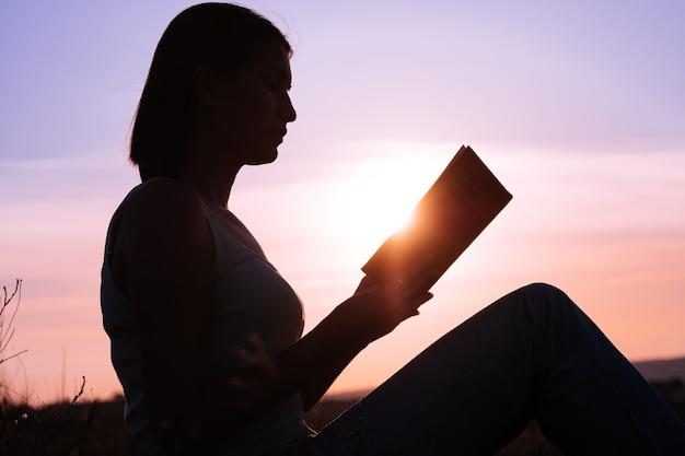 새벽에 젊은 아름 다운 여자의 실루엣 바닥에 앉아 조심스럽게 펼친 책을 쳐다보고