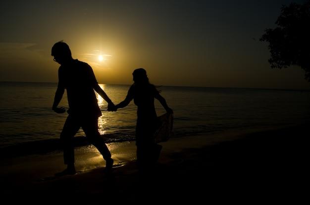Силуэт молодой невесты и жениха на пляже на фоне заката