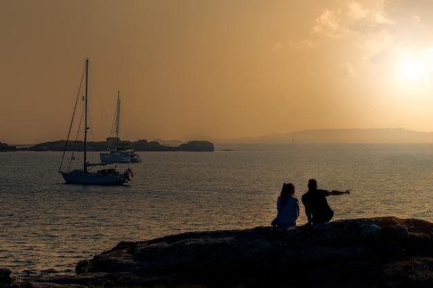 Силуэт молодой пары на пляже, глядя на море на закате