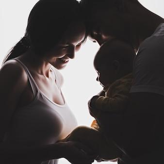 Силуэт молодой семьи, мужчина держит ребенка на руках, невеста стоит перед ним улыбается. концепция новорожденного