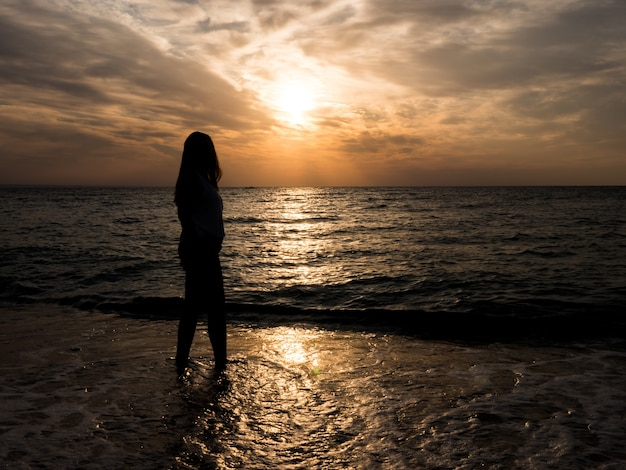 ビーチで若い女の子のシルエット。若い女の子は海のそばで日没で歩いています。休暇中にビーチで観光の女の子