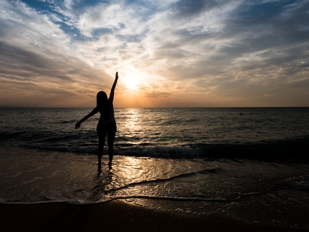 ビーチで若い女の子のシルエット。若い女の子は海のそばで日没で歩いています。ビーチの休日の観光客の女の子。