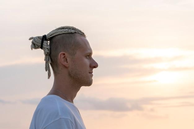 일몰 동안 바다 근처 그의 머리에 향취를 가진 젊은 남자의 실루엣. 초상화를 닫습니다. 열 대 해변에서 향취와 행복 잘생긴 남자