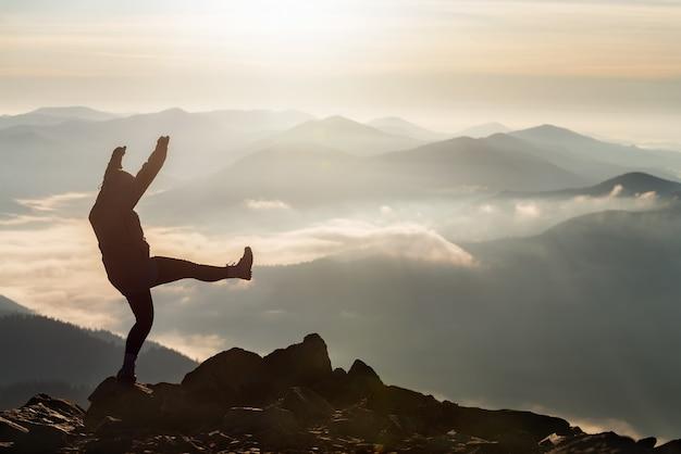 Силуэт молодой счастливой девушки празднует успешное восхождение на вершину горы на восходе солнца.