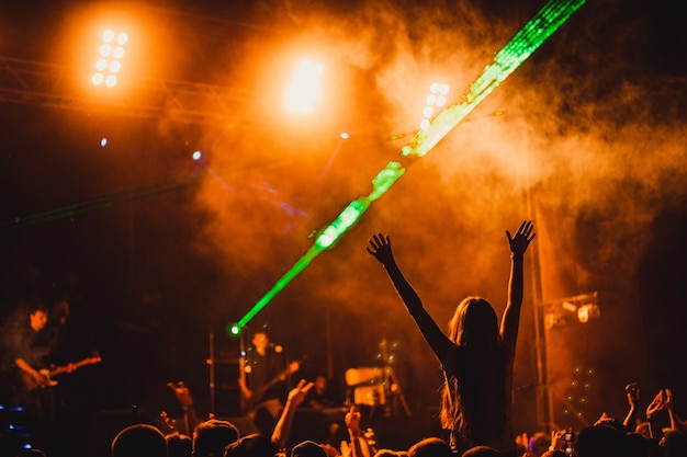 Силуэт молодой женщины в толпе во время концерта