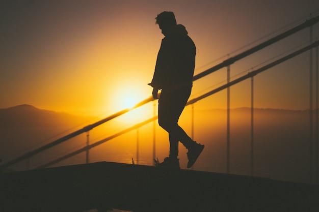美しい夕日の景色と階段のレールの後ろの階段を歩く若い男性のシルエット
