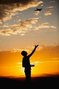 日没の田舎の設定でドローンを操作する若い男のシルエット