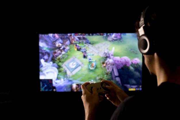 Силуэт молодого человека, играющего в видеоигры, с помощью наушников и консоли