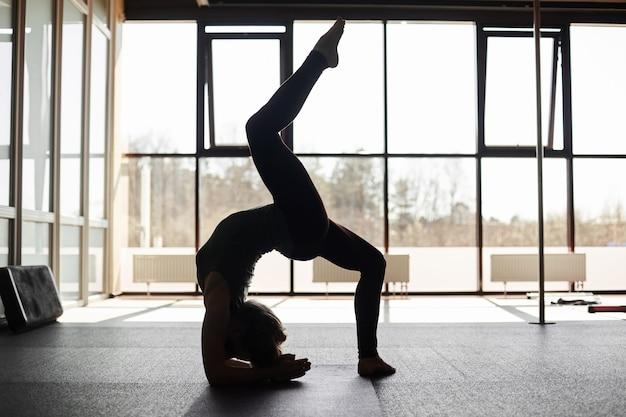 ヨガの概念を練習して、逆立ち、パノラマの窓を実行する若い女性のシルエット