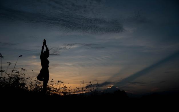 日没時にヨガを練習している若い女性のシルエット