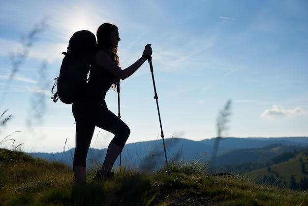 登るアクティブな女の子の登山家のシルエット
