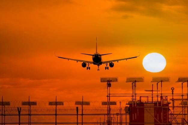 太陽と素晴らしい夕方の空の前に着陸中の飛行機のシルエット