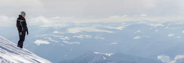 雪山の頂上に立っている一人の観光客のシルエットは、明るい晴れた冬の日に景色と成果を楽しんでいます