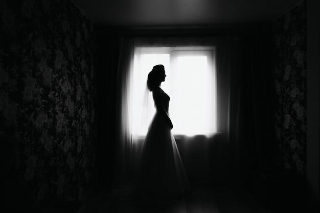 Силуэт элегантной невесты в платье у окна в день свадьбы