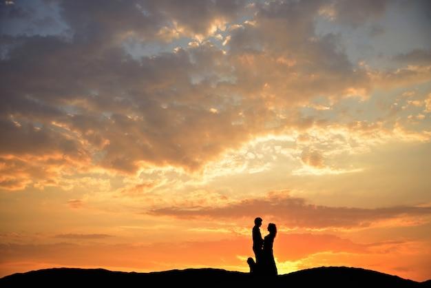 Силуэт до неузнаваемости влюбленная пара с собакой, стоя на песке на фоне заката.