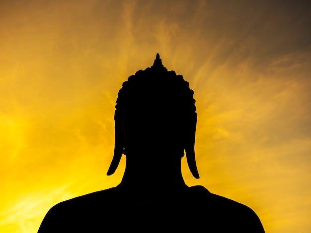 タイのユネスコ世界遺産であるスコータイ歴史公園の黄金の夕焼け空を背景にした古代仏像のシルエット。