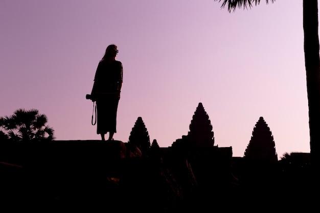 Силуэт ангкор-ват и девушка-путешественница с фотоаппаратом на восходе солнца. ангкор-ват - индуистский храмовый комплекс в камбодже