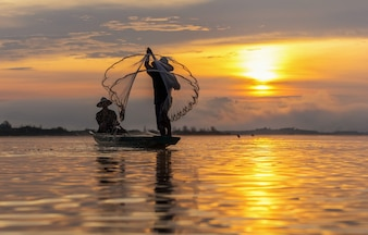 Silhouette of asia traditional fisherman in action when fishing