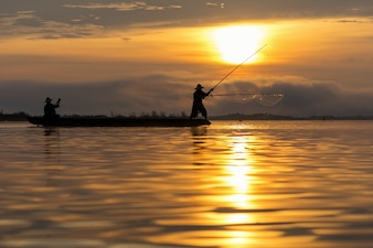 Silhouette of asia traditional fisherman in action
