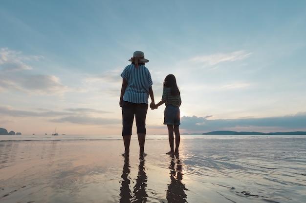 Силуэт азиатской матери и дочери, держась за руку вместе, стоя на пляже, глядя на красивое море и небо во время заката.