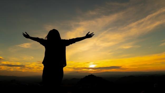 Силуэт азиатской женщины поднимает руки, глядя на гору
