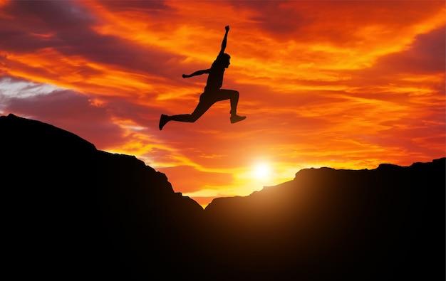 일몰에 대 한 산악 지역에서 바위 위로 점프 선수의 실루엣.
