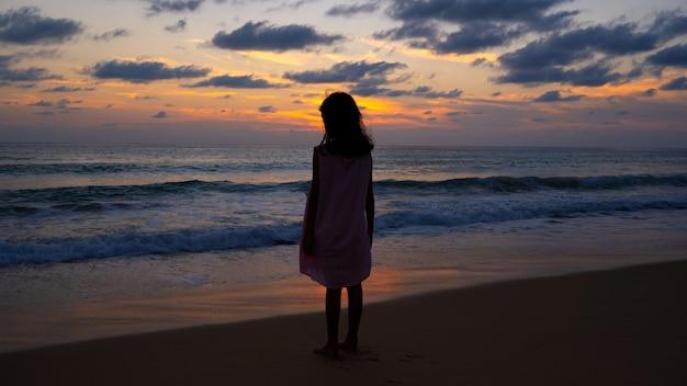 바다에서 일몰이나 일출을 바라보는 해변에 서 있는 여자 아기의 실루엣은 놀라운 빛의 자연 경관 배경입니다.
