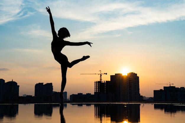 Силуэт балерины, выступающей на фоне городского пейзажа и драматического заката. понятие силы воли, контроля и мечты.
