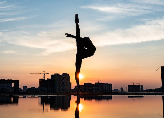 Силуэт балерины, выступающей на открытом воздухе во время заката, концепция мотивации силы воли и желания