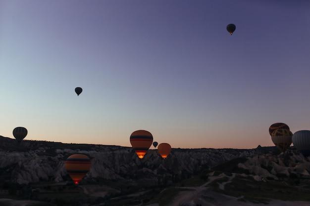 Силуэт красивых воздушных шаров на рассвете в каппадокии